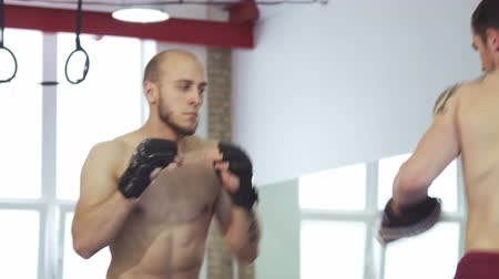 dosažení : Shot of two athletic boxers training together at the gym. Strong male mma fighter boxing at the gym with his coach. Fighting, professional sports career. Masculinity, effort concept.