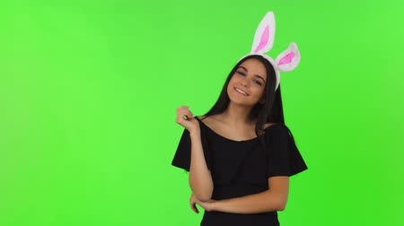 Gorgeous sexy young woman wearing black dress and bunny ears posing playfully on chromakey background. Attractive female model posing confidently. Flirt, dating, romance concept.