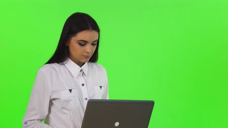 Portrait of a gorgeous young happy businesswoman smiling to the camera, while working on her laptop. Attractive female typing on the computer on chromakey. Technology concept. Stock Footage