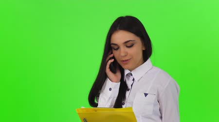 Gorgeous young dark haired businesswoman smiling, talking on the phone posing on chromakey background. Attractive female office worker busy speaking on her smart phone. Стоковые видеозаписи