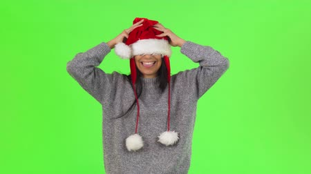 Beautiful happy young woman wearing Santa Claus hat, laughing cheerfully while having fun at studio on chromakey background. Celebration, tradition, lifestyle, season concept. Стоковые видеозаписи
