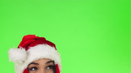 Cropped shot of a cheerful woman wearing Santa Claus hat looking at the copy space. Happy Christmas girl eyes on chromakey background. Advertising, celebration, x-mas concept. Стоковые видеозаписи