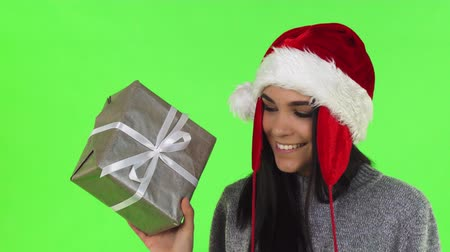 Portrait of a stunning cheerful young woman wearing Santa Claus hat smiling joyfully to the camera, holding Christmas gift box on chromakey. Greeting, congratulations concept.