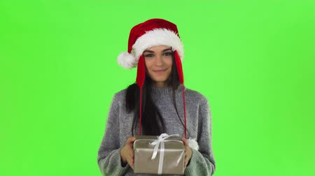 Studio shot of a beautiful happy young Santa woman wearing Christmas hat smiling cheerfully, holding out a present to the camera on chromakey. Celebration, winter, family concept.