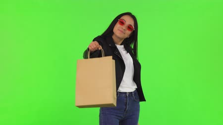 Studio portrait of a gorgeous stylish woman smiling to the camera confidently holding out shopping bag, posing on chromakey background. Consumerism and sales. Shopping mall concept. Стоковые видеозаписи