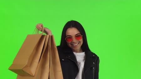 Portrait of a beautiful happy dark haired young woman smiling cheerfully showing thumbs up holding shopping bags posing on chromakey. Excited female customer after shopping on sales.