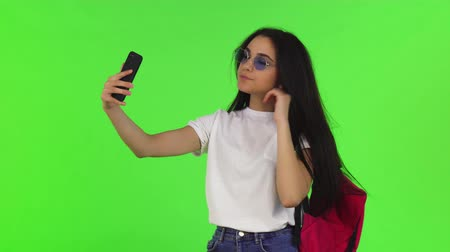 Beautiful long haired female student wearing backpack and eyeglasses, taking selfies using her smart phone, posing on chromakey. Technology, campus, lifestyle, college, high school concept.