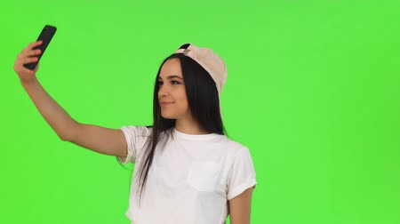 Gorgeous young woman using her smart phone on green background. Attractive cheerful woman smiling, taking selfies with her phone, posing on chromakey. Technology, social media, connection. Стоковые видеозаписи