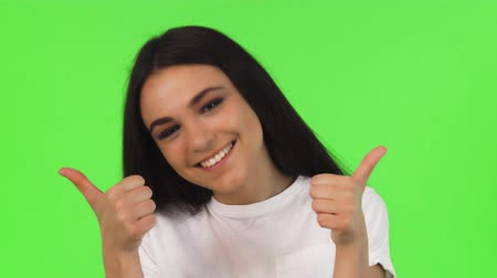 Close up portrait of a happy young beautiful woman smiling cheerfully showing thumbs up. Gorgeous dark haired female smiling joyfully posing on green background. Success, achieving, approved. Стоковые видеозаписи