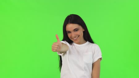 Gorgeous brunette woman in white t-shirt smiling joyfully showing thumbs up posing at studio on green background. Attractive female student showing thumbs up. Success, achievement.