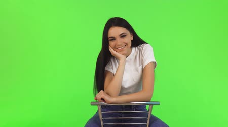 Studio shot of a young gorgeous long haired woman sitting on a chair smiling to the camera happily. Beautiful happy woman posing joyfully on green background. Lifestyle, emotions.