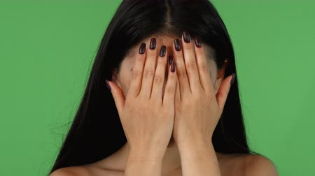 Close up portrait of a beautiful young Asian woman posing expressively on green chromakey background. Attractive expressive woman hiding her face in her hands, showing different emotions.