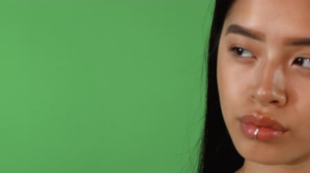 Sliding cropped shot of a gorgeous young Asian woman with flawless skin and lip ring piercing posing confidently on green chromakey background, looking away. Copy space on the side.
