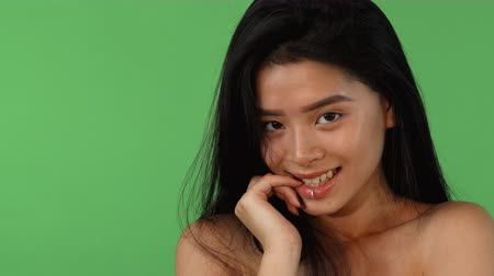 Studio shot of a gorgeous young Asian woman posing sensually on green chromakey background, biting her finger seductively, smiling to the camera. Playful seduction concept.