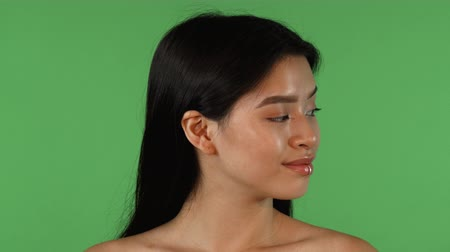 Attractive young Asian woman looking to the sides, while posing on green chromakey background, then smiling confidently to the camera. Confidence, femininity, youth concept.