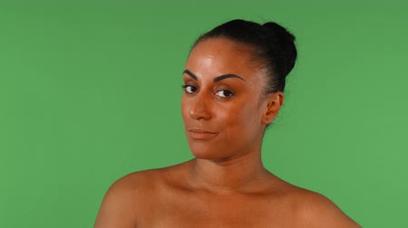 Studio shot of a beautiful mature African woman disappointed, looking to the camera skeptically. Attractive mulatto female looking upset, posing on green chromakey. Emotions, angry concept.