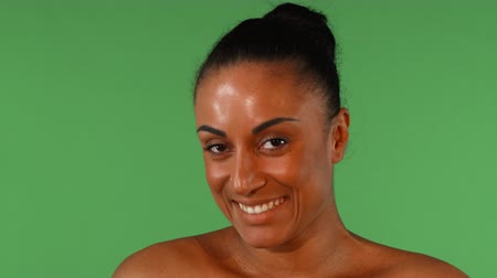 Studio portrait of a gorgeous African mature woman smiling, looking to the camera playfully. Beautiful mulatto female laughing joyfully, posing on green chromakey background.