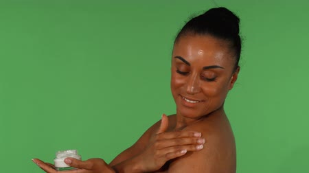Beautiful mature African woman enjoying applying moisturizing body lotion. Happy gorgeous mulatto woman smiling cheerfully while using body cream. Beauty, health, skincare concept.