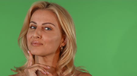 Portrait of a mature beautiful blonde woman smiling joyfully to the camera looking thoughtful on green chromakey, copy space. Femininity and maturity concept. Confidence and success. Stock Footage