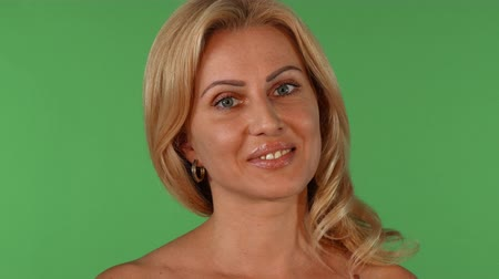 Studio portrait of a stunning sexy blond haired mature female smiling joyfully to the camera, posing gracefully on green chromakey background at studio. Seduction, sexuality concept.