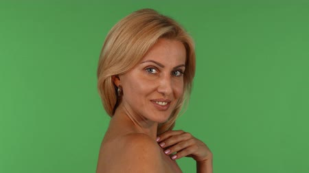 Studio portrait of a gorgeous mature woman smiling to the camera seductively, touching her skin sensually. Sexy mature female posing gracefully on green chromakey background.