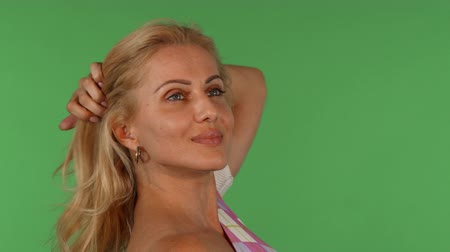 Studio shot of a stunning mature beautiful woman smiling joyfully, looking away while playing with her hair, posing gracefully on green chromakey background. Femininity, beauty, health concept. Стоковые видеозаписи