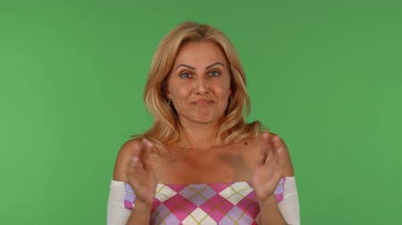 Studio portrait of a gorgeous mature female looking surprised and sorry, posing on green chromakey background. Beautiful female expressing guilt at studio. Expressing emotions concept.