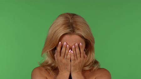 Studio portrait of a gorgeous blond haired woman showing different emotions, posing on green chromakey background. Attractive expressive woman at studio. Character, expression concept. Стоковые видеозаписи
