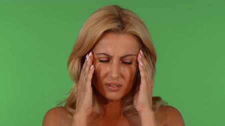Studio shot of a stunning beautiful mature blond haired woman having headache, rubbing her temples. Gorgeous female having migraine, posing on green chromakey. Stock Footage