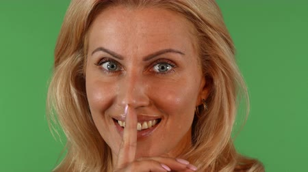 Gorgeous mature woman smiling seductively, shushing to the camera. Beautiful female looking playfully to the camera with her finger to her lips on green chromakey background. Stock Footage