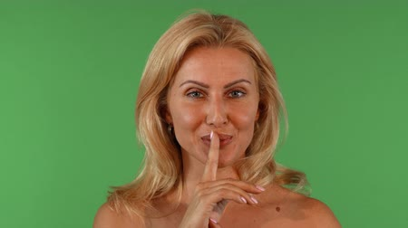 Studio portrait of a gorgeous mature blond haired woman posing sensually on green chromakey, smiling joyfully and shushing to the camera, putting her finger to her lips.
