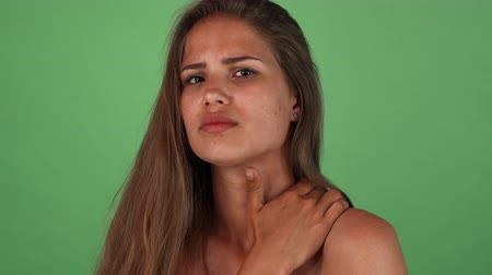 nervous breakdown : Stunning beautiful young woman looking upset, having upper back pain. Gorgeous female posing on green chromakey, feeling sick, rubbing her shoulder. Health, medicine, treatment concept.