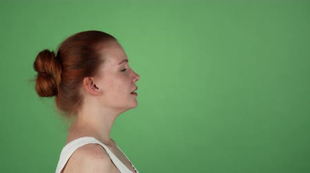 gritar : Profile portrait of a young red haired woman screaming furiously on green chromakey background. Ginger haired female shouting angrily. Stress, depression, nervous breakdown concept.