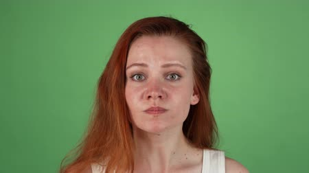 gritar : Studio portrait of a young red haired woman looking angry. Ginger female arguing with you, posing on green chromakey background. Conflict, emotions, misunderstanding concept.