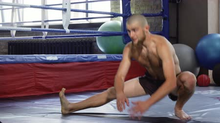 erkeklik : Young bearded kickboxer stretching his legs before training. Professional mma fighter exercising at sports studio. Athletic young man working out in front of the boxing ring. Sports, activity concept. Stok Video
