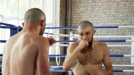 konkurenti : Rear view shot of a shirtless bearded male mma fighter training at the gym. Professional male boxer practicing punches in front of the mirror at the gym. Effort, agility, energy concept. Dostupné videozáznamy