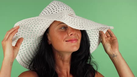 шелковистый : Beautiful happy woman wearing summer beach hat, smiling joyfully to the camera on green background. Attractive female posing elegantly on chromakey. Summertime, vacation concept.