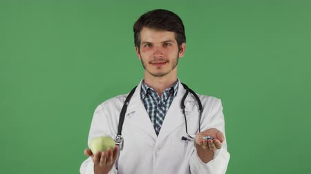 fidedigno : Male doctor offering medications or healthy food. Handsome bearded therapist wearing labcoat, holding an apple and medications, posing on green chromakey background.