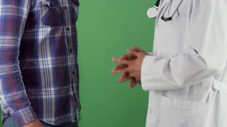 professionalism : Cropped shot of a man shaking hands with his therapist on green chromakey background. Male doctor shaking hands with his patient after successful recovery. Healthcare service.