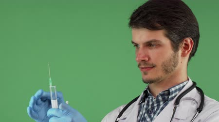 fidedigno : Cropped shot of a handsome bearded male doctor preparing syringe for an injection. Attractive therapist posing with a syringe on chromakey background. Medicine, healthcare, vaccination concept.
