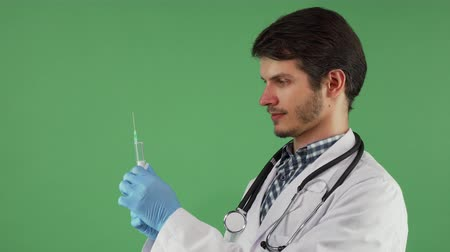professionalism : Male doctor preparing to make an injection with the syringe. Handsome practitioner holding an injector filled with vaccine. Medicine, healthcare, professionalism concept.