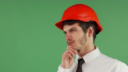 professionalism : Portrait of a young handsome bearded foreman wearing protective hardhat looking away thoughtfully, rubbing his beard on chromakey background, copy space on the side. Stock Footage