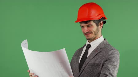 professionalism : Portrait of a young handsome bearded male architect wearing protective hardhat smiling joyfully while examining his blueprints. Proud engineer posing confidently on green chromakey.