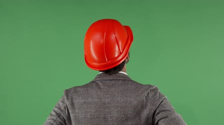 professionalism : Cropped rear view shot of a male engineer in protective hardhat looking at the green chromakey screen. Professional architect looking around. Occupation, building industry concept.