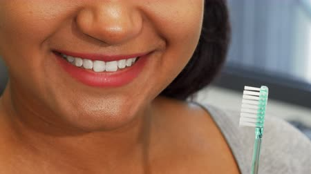 proteza : Cropped shot of a cheerful African woman smiling happily with her perfect white teeth, holding a toothbrush near her mouth. Cheerful female with healthy smile. Teeth care, whitening concept.