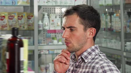 boticário : Portrait of a young handsome man shopping at the drugstore, examining products on the shelves. Attractive male customer buying medicine at the pharmacy. Health, medicine, consumerism.