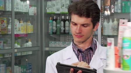 professionalism : Young handsome male pharmacist working at the drugstore. Cheerful professional pharmacist smiling to the camera while doing inventory at the pharmacy, using digital tablet.