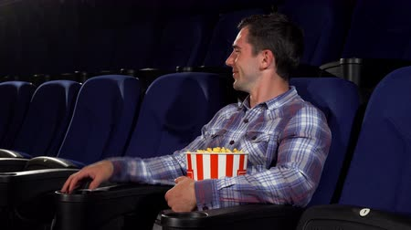 néző : Cheerful handsome man relaxing at the movie theatre. Happy young man smiling to the camera holding his popcorn bucket sitting at the cinema. Entertainment, lifestyle, recreation concept.