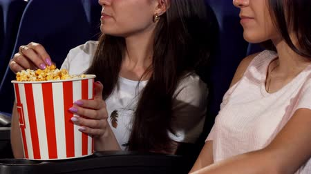 благополучия : Cropped shot of two female friends enjoying watching comedy movie at the cinema. Happy women eating popcorn, laughing cheerfully at the movie theatre. Friendship, food concept. Стоковые видеозаписи