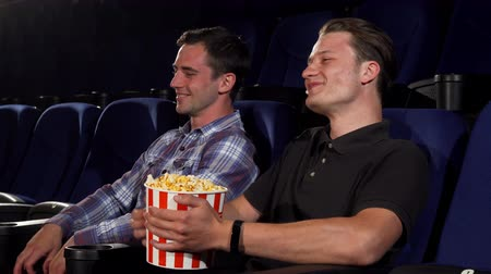 зрителей : Young handsome man laughing joyfully talking to his friend while watching comedy movie at the cinema. Cheerful male friends eating popcorn at the movie theatre. Entertainment concept. Стоковые видеозаписи